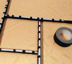 LED-Leisten mit schwarzem Klebeband auf dem Rahmen befestigen